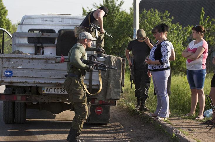 Ante la vista de civiles, rebeldes pro rusos bajan de un vehículo para apoyar a sus compañeros en un retén en las afueras de la ciudad de Slovyansk, en el este de Ucrania.Elpais.com.co | AP