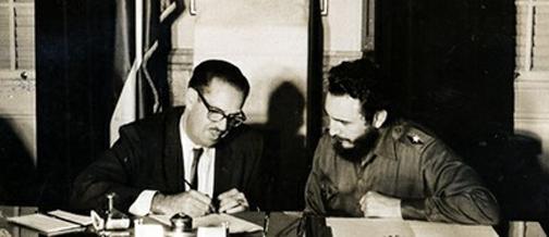 El anodino presidente de Cuba, Dr. Osvaldo Dorticós Torrado, firma el 6 de julio de 1960 la Ley No. 851 de expropiación de propiedades norteamericanas legítimamente establecidas en territorio nacional de La Isla, ante la mirada atenta de Fidel Castro Ruz, a la sazón Primer Ministro del Gobierno Revolucionario Cubano.