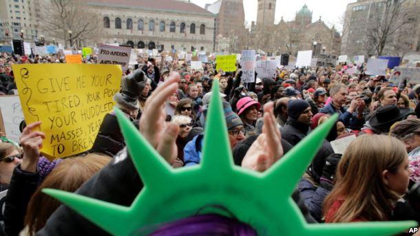 En Boston, un manifestante lleva un sombrero de la Estatua de la Libertad y aplaude durante una manifestación celebrada en protesta contra la orden del presidente Donald Trump que restringe el viajes a los Estados Unidos.