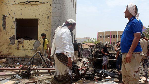 Varios sobrevivientes caminan sobre los escombros que quedaron luego de un atentado en Yemen (AP)