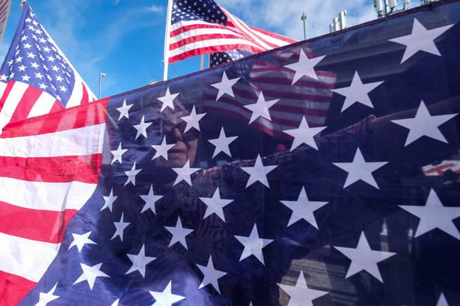 Mandy Adams, de 70 años, sostiene banderas de EEUU en una movilización a favor de las políticas de Trump. (Reuters)