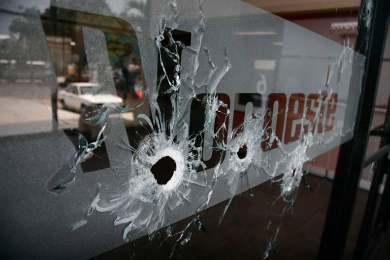 La entrada del diario <i>Noroeste</i> quedó impactada por orificios de bala luego de que sujetos armados abrieron fuego contra la sede regional del periódico en la turística ciudad de Mazatlán, en la costa del Pacífico mexicano, el 1 de septiembre de 2010. (AP/Christiann Davis)