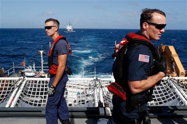 En esta foto del 7 de marzo de 2017, dos miembros de la Guardia Costera de Estados Unidos observan cómo son transferidos algunos sospechosos del guardacostas Stratton al guardacostas Mohawk, al fondo, mientras navegan en aguas del océano Pacífico.
