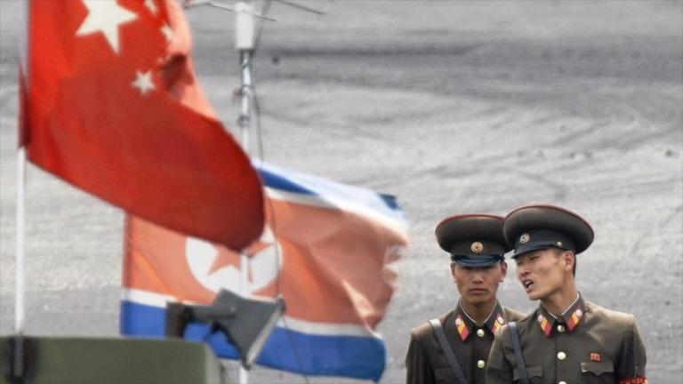 Soldados norcoreanos al lado de las banderas nacionales de China y Corea del Norte en la frontera que comparten ambos países.