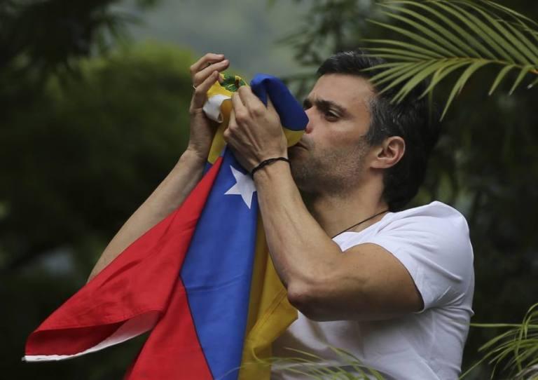 Leopoldo López desde la terraza de su casa besando la bandera de Venezuela