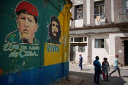 """People pass by images depicting Venezuela's late president Chavez and late revolutionary hero """"Che"""" Guevara in downtown Havana"""