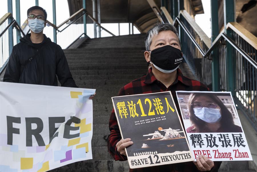 Activistas por la democracia en Hong Kong se encuentra cerca de la Oficina de enlace del Gobierno Chino mientras sostiene carteles en apoyo a la ciudadana china Zhang Zhan, arrestada por informar sobre el Covid-19. (Efe) 100 millones de infectados