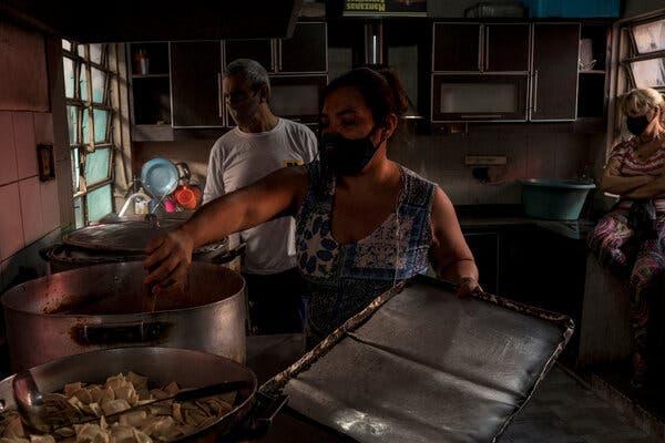 Voluntarios en otro comedor de beneficencia en el vecindario de la Sra. Huanca.  Ella y su familia han necesitado ayuda para tener comida en la mesa.